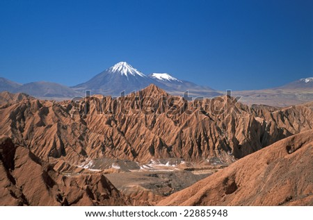 Natural rock formations of the Atacama Desert and beyond the snow capped peaks of the Western Cordilleras.