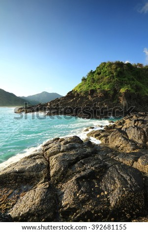 Natural rock with strong water wave and sunrise background at Selong Belanak Beach, Lombok, Indonesia - stock photo