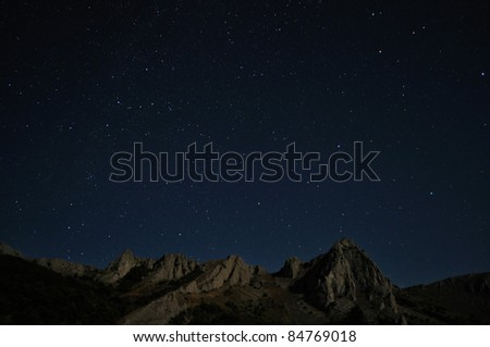 Natural rocks and stars at night in the mountains - stock photo