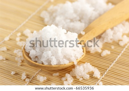 Natural salt of Dead Sea in wooden spoon on mat.
