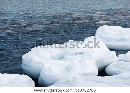 Natural sea ice blocks breaking up against shore and ice during freezing winter weather. Arctic aquatic nature  - stock photo