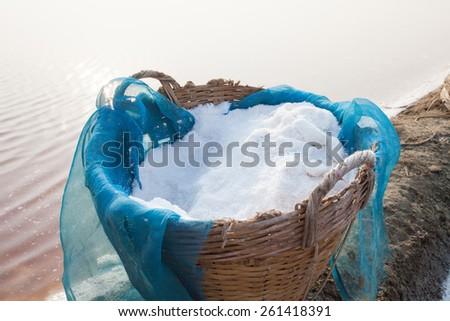 natural sea salt in thai bamboo basket original harvest container in sea salt farm  - stock photo