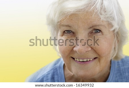 Natural senior woman portrait on yellow background - stock photo