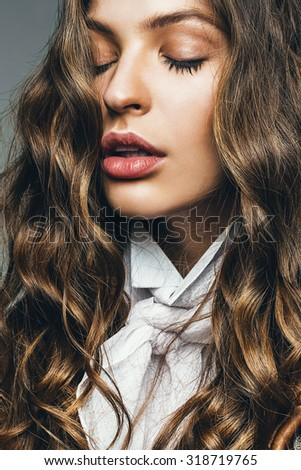 natural sensual woman with long curly hair in studio