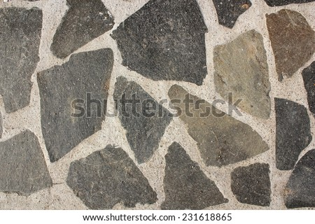 natural shaped stones on cement texture, pavement on the street - stock photo