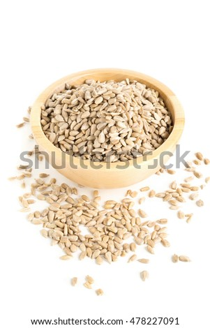 Natural shelled sunflower seeds in wooden bowl over white background