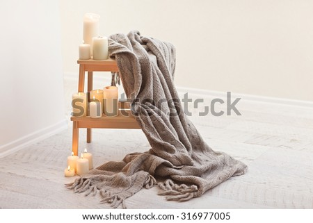Natural small wooden ladder on white wood floor with grey pleid and burning candles on it. - stock photo