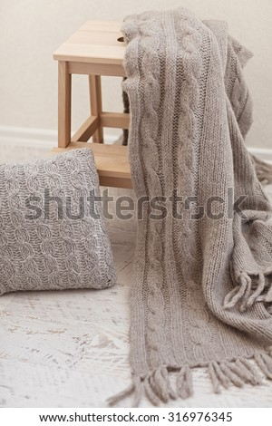Natural small wooden ladder on white wood floor with grey pleid and wollen pillow - stock photo