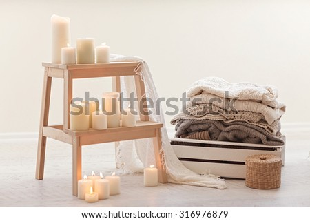 Natural small wooden ladder on white wood floor with warm wool sweaters and burning candles on it.