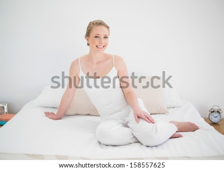 Natural smiling blonde sitting on bed in bright bedroom