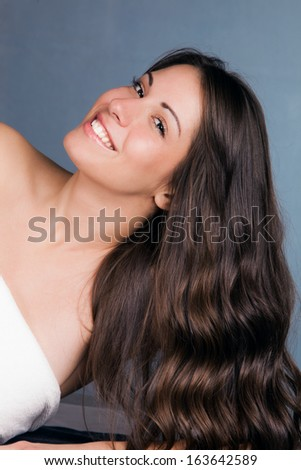 natural smiling looking girl with long brown shiny hair