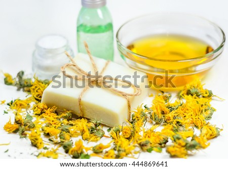 Natural soap bar on dry yellow flowers at olive oil and bottles background. Spa treatment and skin care - stock photo