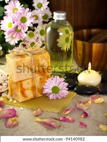 Natural soap from honey. Olive oil, massage stones with a candle, mortar with a pestle. Health spa for spa treatment. - stock photo