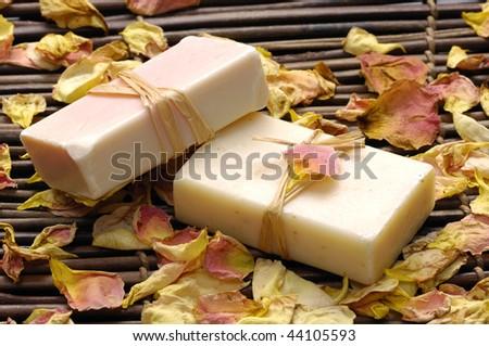 Natural soap with petals on bamboo mat - stock photo
