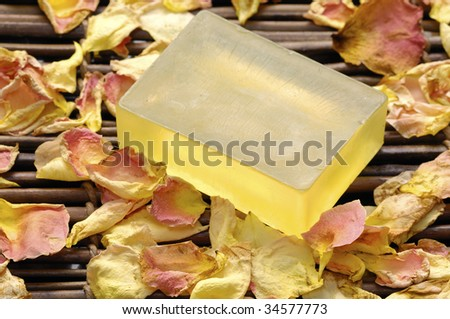 Natural soap with petals on mat - stock photo