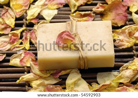 Natural soap with rose petals on mat - stock photo
