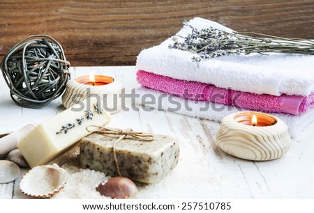 Natural Spa and Wellness Product on Wooden Background with Burning Candles, Towel,Homemade Soap and Lavender Bouquet, selective focus - stock photo