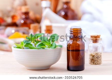 Natural Spa Ingredients essential oil with oregano leaves for aromatherapy setup on spa ingredients background. - stock photo