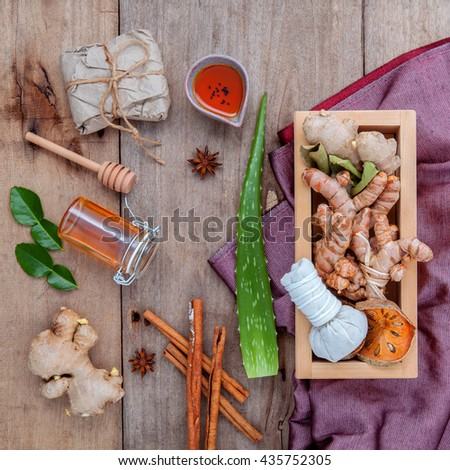 Natural Spa Ingredients herbal compress ball and herbal  Ingredients  for alternative medicine and relaxation Thai Spa theme with silk fabric on old wooden background. - stock photo