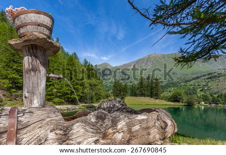 Natural spring water and small alpine lake in Piedmont, Northern Italy. - stock photo