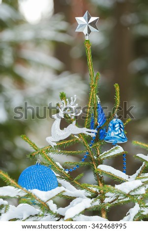 Natural spruce tree in snowy forest decorated with Christmas ornaments and silver star finial  - stock photo