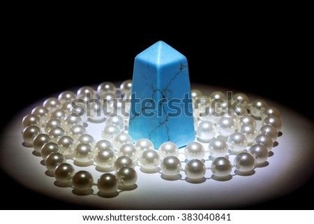 Natural stone and pearl necklace on a dark background - stock photo