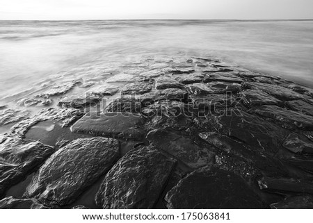 Natural stone jetty in sea - stock photo