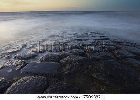 natural stone jetty in sunset - stock photo
