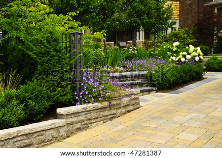 Natural stone landscaping in front of a house with lush green garden - stock photo