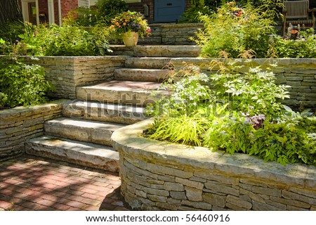 Natural stone landscaping in home garden with stairs - stock photo