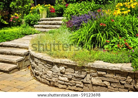 Natural stone landscaping in home garden with stairs and retaining walls - stock photo