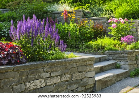 Natural stone landscaping in home garden with steps and flowerbeds - stock photo