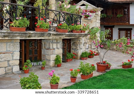 Natural Stone Landscaping In The Backyard And Many Flowers In The Pot - stock photo