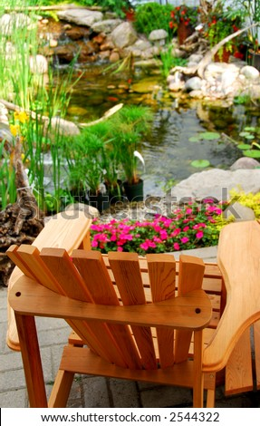 Natural stone pond and wooden patio chair as landscaping design element - stock photo