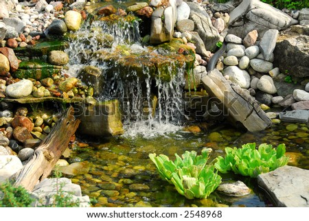Natural stone pond as landscaping design element - stock photo