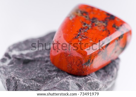 natural stone red jasper in beautiful colors on white ground - stock photo