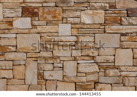 Natural stone wall pattern or background. The wall was designed and constructed with a high degree of craftsmanship. Marble, granite, slate stone material. Mostly gray and a few reddish, beige stones. - stock photo