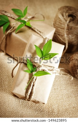 Natural style handcrafted gift boxes with rustic twine on burlap - stock photo