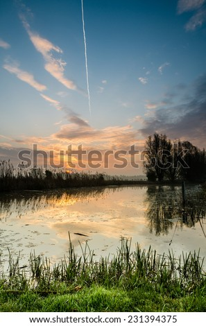 Natural sunrise with wooden picknic bench  - stock photo