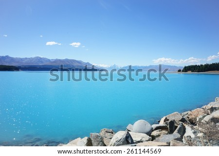 Natural turquoise Lake Tekapo, travel destination, under blue sky - stock photo