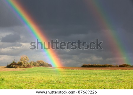 Natural two rainbow over green field and dark sky - stock photo