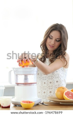 Natural, vitamins. Cute, attractive woman making orange juice - stock photo