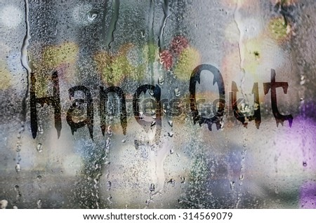 "natural water drops on glass window with the text ""Hang Out"" - stock photo"