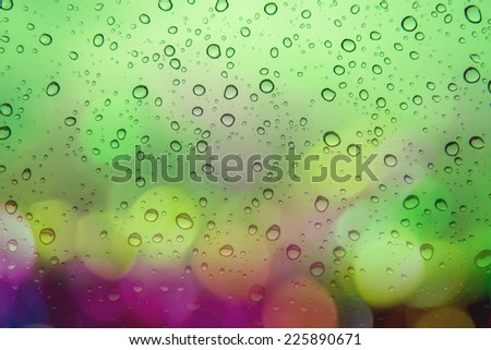 Natural water drops on  green window glass background with Multicolored defocused bokeh lights at Night - stock photo