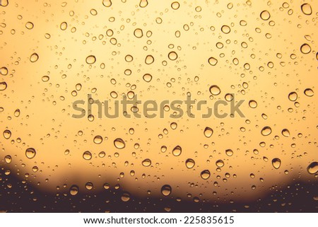 Natural water drops on orange colour  window glass background - stock photo