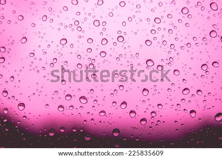Natural water drops on pink  window glass background - stock photo
