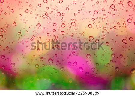 Natural water drops on red window glass background with Multicolored defocused bokeh lights at Night - stock photo