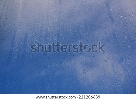 Natural water drops on window glass with sky's background - stock photo