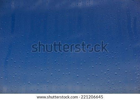 Natural water drops on window glass with sky's background