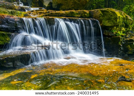 natural waterfall and green mossy stones - stock photo